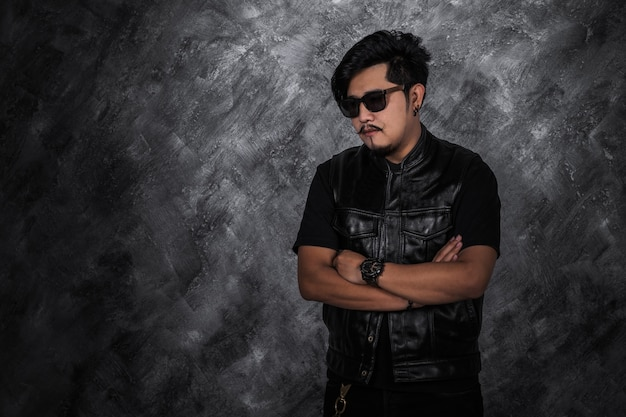 Portrait of biker man in black leather jacket with arms crossed
