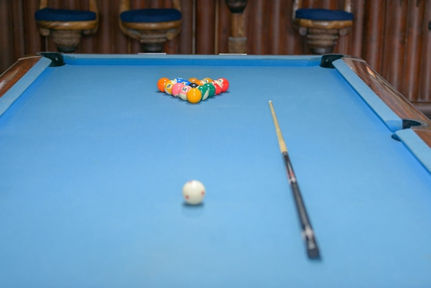 Portrait of billiard table with cue and balls ready for playing