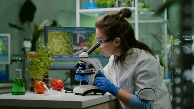 Portrait of biologist scientist in white coat working in expertise laboratory looking into microscope analyzing organic gmo leaf