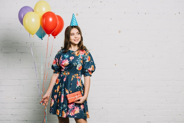 Portrait of a birthday girl holding balloons and gift box looking away