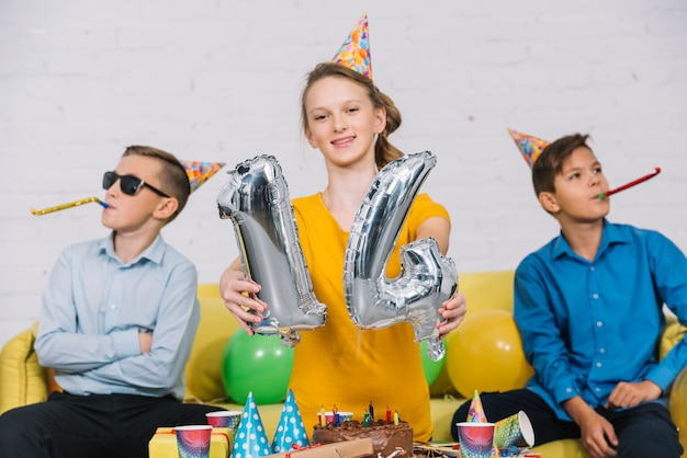 Portrait of a birthday girl showing numeral 14 foil balloon with her two friends blowing party horn