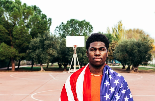 Portrait of a black african-american boy carrying the u.s. flag on an urban basketball court.