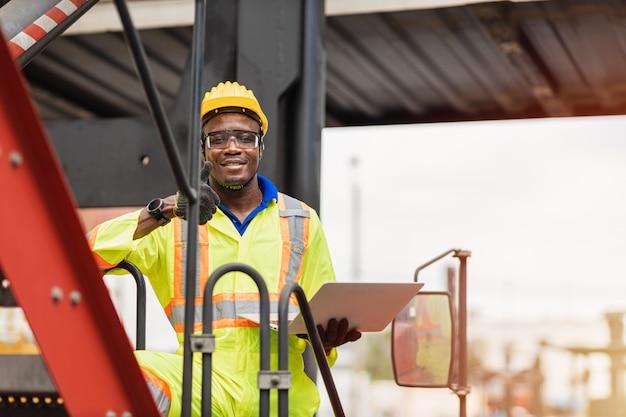 Улыбка чернокожего африканского штатного работника портрета счастливая работая в логистическом порту доставки грузового крана.