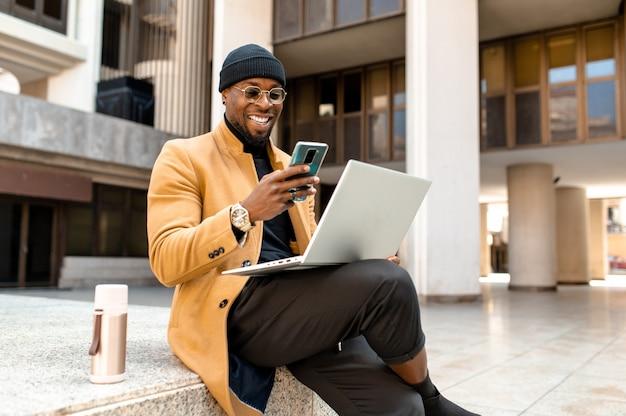 Портрет черный бизнесмен в элегантной стильной одежде, сидя на ступенях в городе и с помощью портативного компьютера. парень улыбается во время чата со смартфоном.