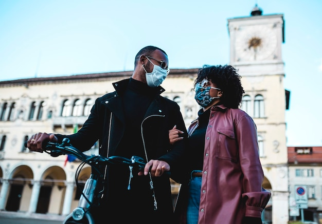 Portrait of black ethnic couple with protective mask and bicycle.