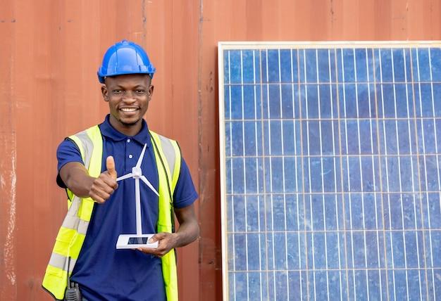 배경에 풍차 모델 컨테이너와 태양 전지를 들고 세로 흑인 남자 엔지니어링