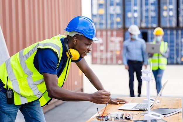 Портрет чернокожего инженера с контейнером для модели ветряной мельницы и солнечной батареей на заднем плане