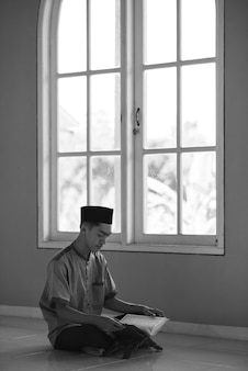 Portrait black and white image of young asian muslim man reading holy qur'an on ramadan kareem at the mosque