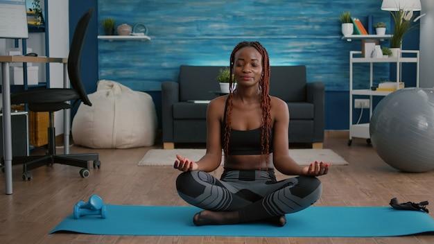 Ritratto di donna nera seduta nella posizione del loto sul pavimento facendo allenamento di respirazione mattutina