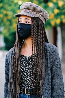 Portrait of black woman with braids using a protective mask during coronavirus pandemic