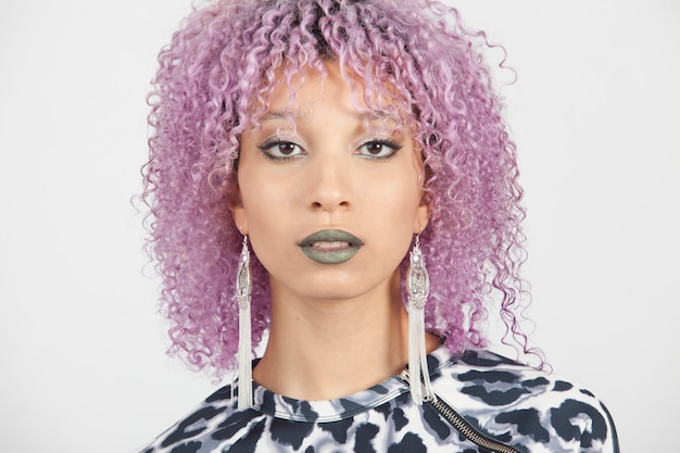 Portrait of a black woman with elegant earrings, sensual blue lips and purple afro hair