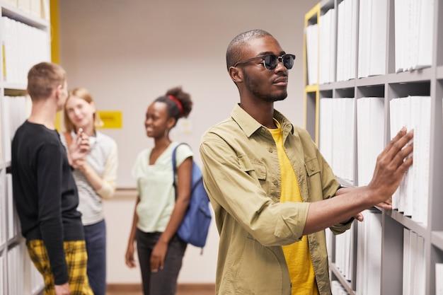 Portrait of blind africanamerican man choosing book in library