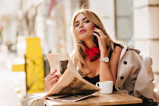 Ritratto di beata ragazza bionda che riposa nella caffetteria e parla al telefono con un amico