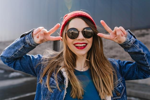 Ritratto di ragazza beata con capelli dritti chiari che ride. foto di donna bianca allegra con gli occhiali in posa sulla strada in una giornata di sole.