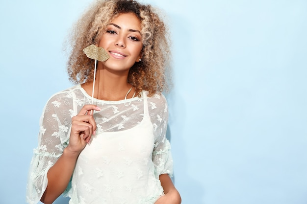 Portrait of blissful lovable woman with blond african hairstyle with big lips on stick.