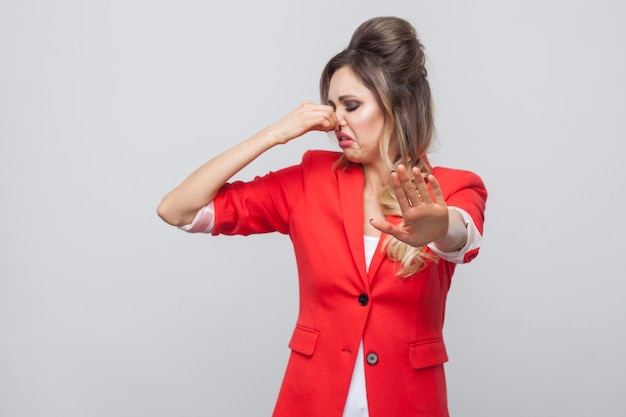 Portrait of blocking beautiful business lady with hairstyle and makeup in red fancy blazer, standing with stop gesture and closing her nose. indoor studio shot, isolated on grey background.