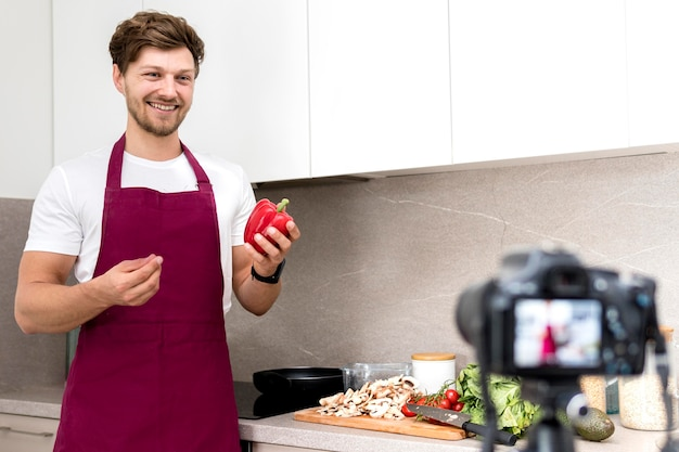 Portrait of blogger recording cooking video at home
