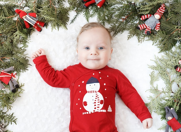 Portrait of a blond baby with christmas toys