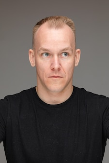 Portrait of a blond caucasian man in black t-shirt looking away with his eyes wide-open showing surprise or shock.