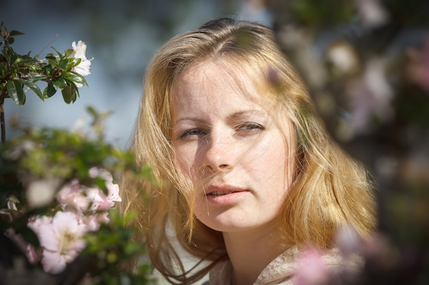 Portrait of a blond girl among the flowers of azalea in the rays of sunlight