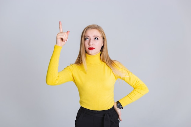 Portrait blond woman standing against gray background. she has an idea. copy space