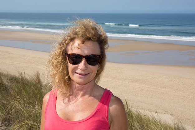 Portrait of a blond woman in sun glasses on the beach