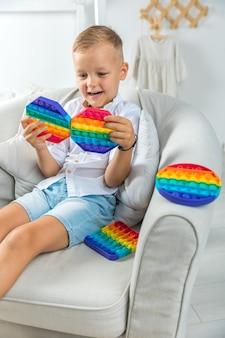 ポップイット感覚おもちゃのさまざまな形で肖像画の金髪の少年