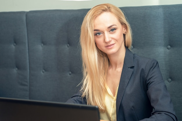 Portrait of blonde businesswoman is sitting in sofa and surfing on internet.