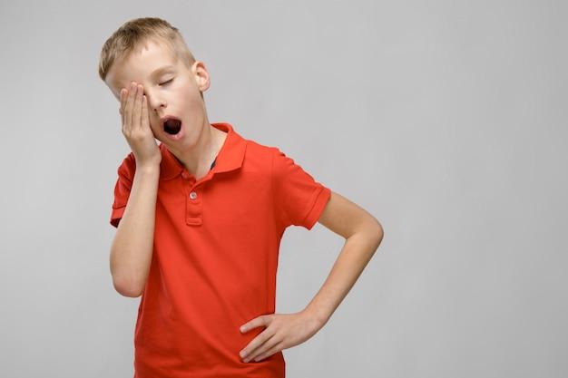 Portrait of blonde caucasian sad little boy in orange tshirt wanting to sleep yawning on gray