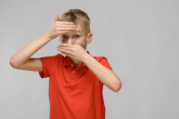 Portrait of blonde caucasian sad sick little boy in orange t-shirt closing his forehead and mouth with hands