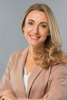 Portrait of blonde confident young businesswoman against gray background