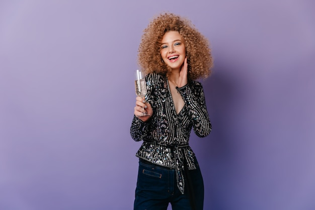 Portrait of blonde curly girl in shiny black blouse laughing and holding glass of white wine on purple space.