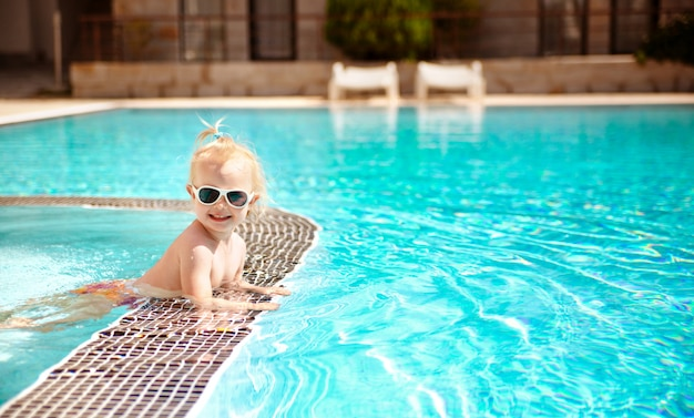 The portrait of a blonde cute baby in sunglasses, swimming in the pool at summer holidays.