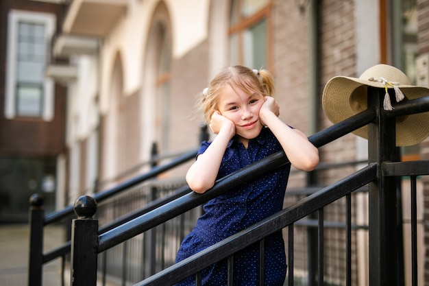 Portrait of blonde girl 10 years old playing among beautiful old houses