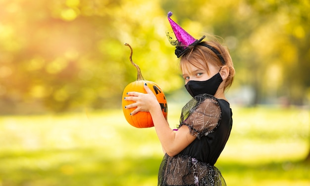 Portrait blonde girl in witch costume with pumpkin in her hands. halloween kids wearing mask.