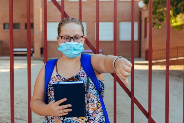 Portrait of a blonde girl with a blue backpack and a face mask.thumb down symbol. back to school.