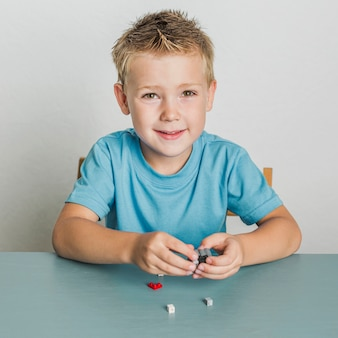 Portrait of blonde hair child with lego