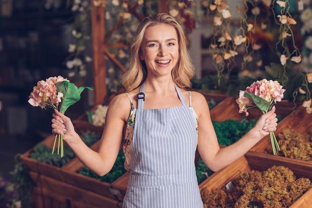 Portrait of a blonde happy female florist holding pink hydrangea bouquet in two hands
