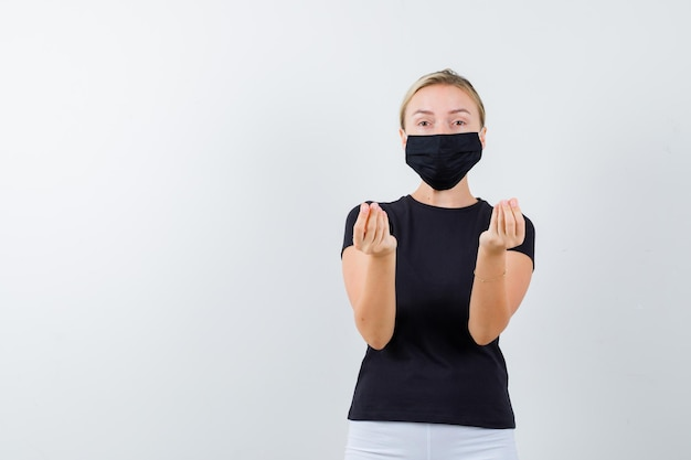 Portrait of blonde lady doing italian gesture in black t-shirt isolated