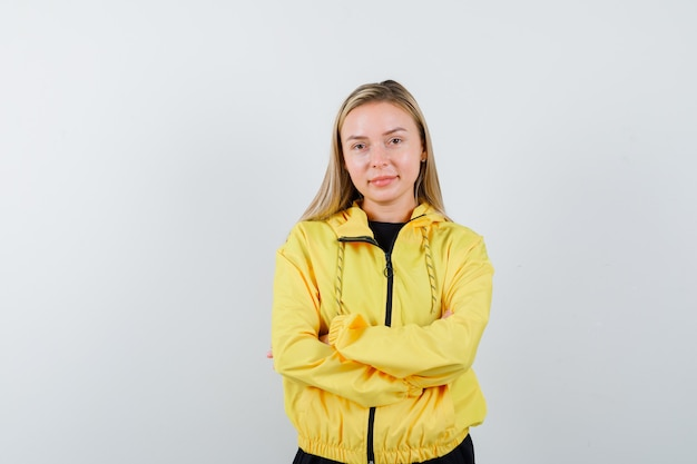 Portrait of blonde lady holding arms folded in tracksuit and looking confident front view
