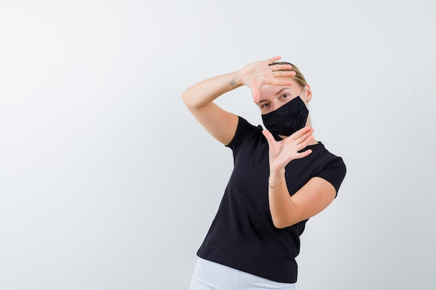 Portrait of blonde lady making frame gesture in black t-shirt isolated