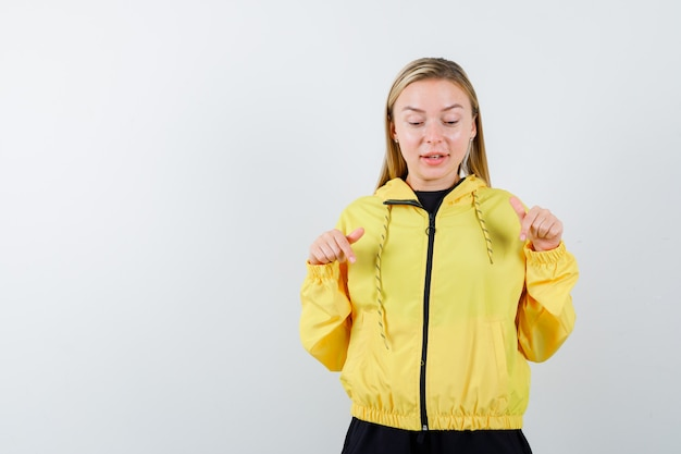 Ritratto di signora bionda con la punta rivolta verso il basso in tuta da ginnastica e guardando stupito vista frontale