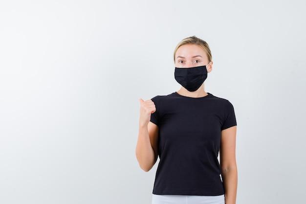 Ritratto di signora bionda che punta il pollice indietro in maglietta nera isolata