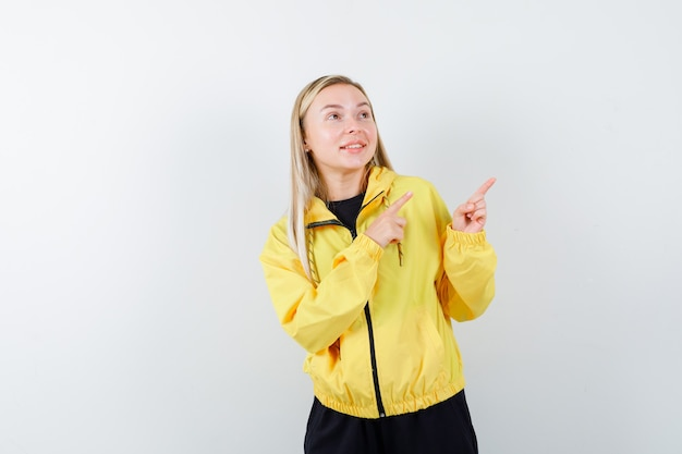 Portrait of blonde lady pointing at upper right corner in tracksuit and looking astonished front view