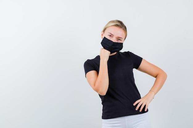 Ritratto di signora bionda che sostiene il mento a portata di mano in maglietta nera