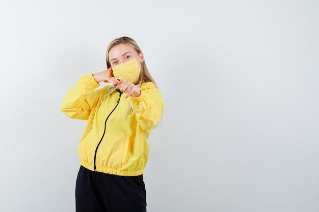 Ritratto di signora bionda che mostra il gesto del telefono, indicando la telecamera in tuta e guardando fiducioso vista frontale