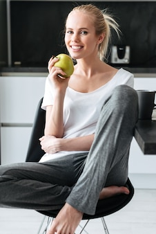 Portrait of blonde lady sitting and looking in kitchen