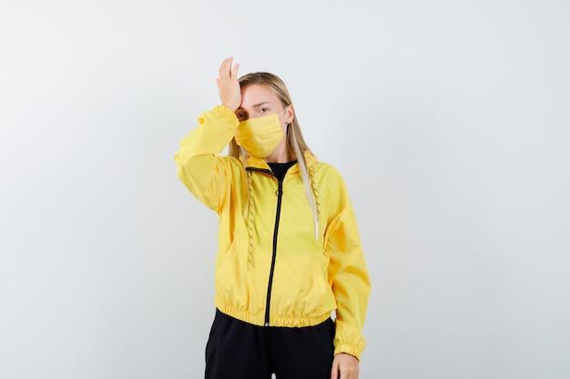 Ritratto di signora bionda che soffre di mal di testa in tuta da ginnastica, maschera e vista frontale dall'aspetto stanco