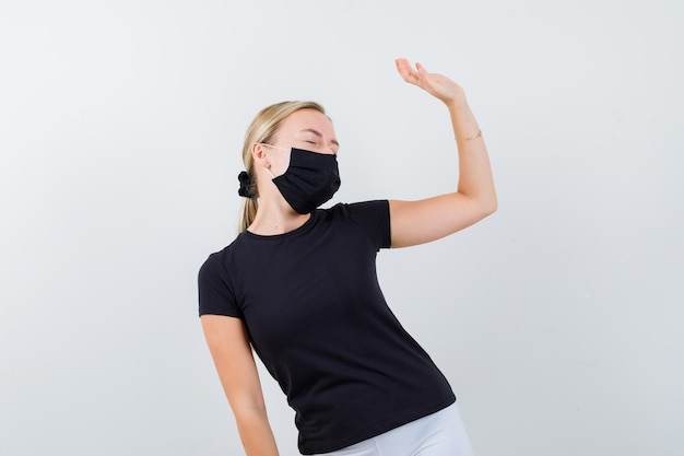 Portrait of blonde lady waving hand while closing eyes isolated