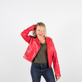 Portrait of blonde mature woman in red leather jacket standing against white background